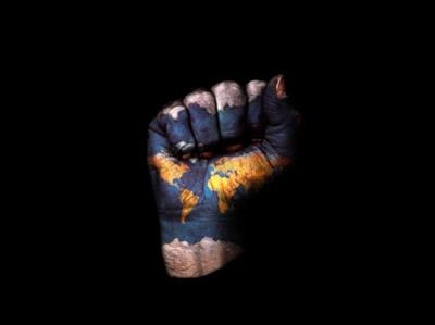 A fist with a map of the earth painted on it, on a black background