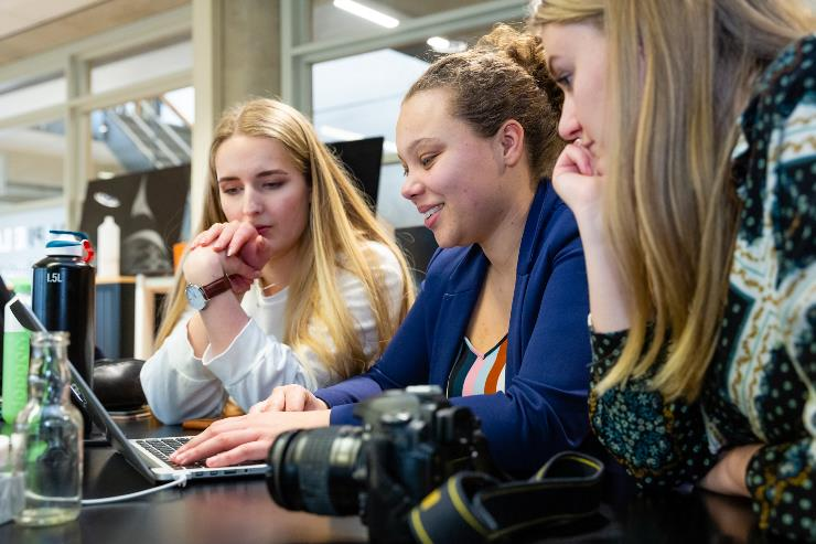 three students working on a digital project