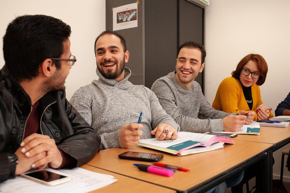 four students sitting in a classroom, laughing
